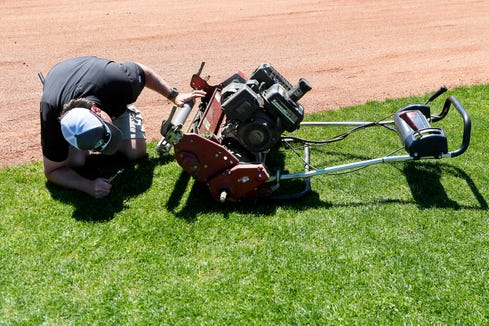 Scott Beam, an assistant coach for Reynolds High School baseball, tinkers with a lawnmower at the school's baseball field April 10, 2019.