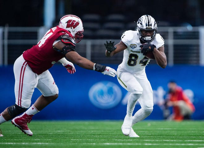 Wisconsin Badgers defensive end Chikwe Obasih (34) and Western Michigan Broncos wide receiver Corey Davis (84) in action in the 2017 Cotton Bowl game at AT&T Stadium. The Badgers defeat the Broncos 24-16.