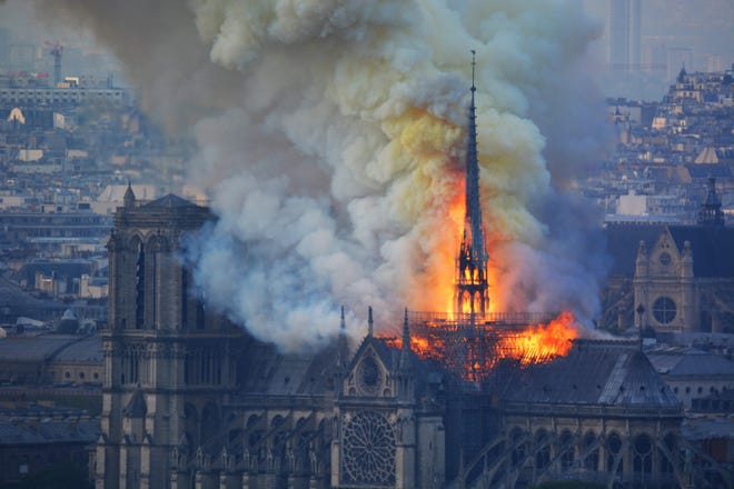 Smoke and flames rise during a fire at the landmark Notre-Dame Cathedral in central Paris on April 15, 2019. The flames and smoke plumed from the spire and roof of the gothic cathedral, where renovations are currently underway.
