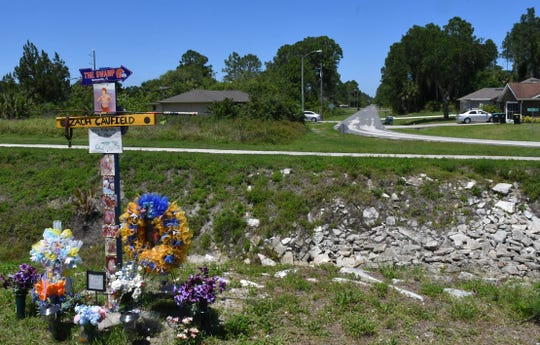 The temporary roadside memorial along Malabar Road in Palm Bay to  Zach Caufield, 19, who was killed at night in a crash where Hoffer Avenue (seen in background) ends at the Melbourne Tillman Canal system.
