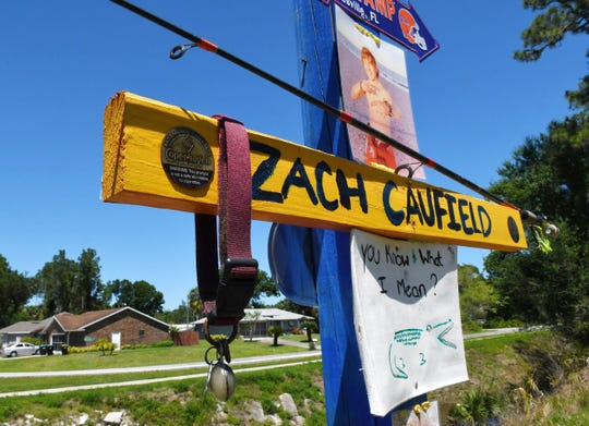 The temporary roadside memorial along Malabar Road in Palm Bay to Zach Caufield, 19, who was killed at night in a January crash where Hoffer Avenue ends at the Melbourne Tillman Canal system. The collar hanging at left is from his dog, Drac, who died a couple of months later.