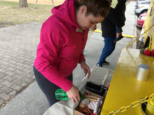 Allyssa King of St. Albans sprays vinegar on her French fries at Beansie's Bus in Burlington on April 16, 2019.