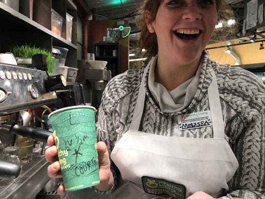 Melissa Cohen shows off a drink she made for another coworker, Courtney, at Healthy Living Market & Cafe. April 3, 2019.