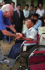 Sen. Patrick Leahy, D-Vt., in 1996,  shakes hands with a Vietnamese man injured by a landmine gets who received his first wheelchair at a clinic in Vietnam funded through the Leahy War Victims Fund.