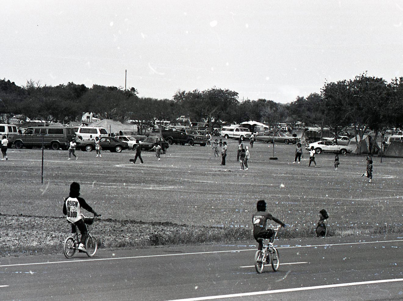 Kids on bikes ride past the recreation fields at Nueces River Park in Corpus Christi, which was packed with families enjoying Easter Sunday on April 19, 1987.