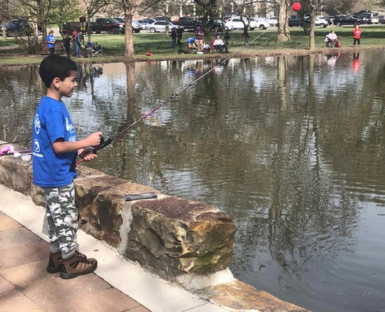 A boy fishes in Yoctangee Park during the annual Fish with a Firefighter event on Saturday, April 13, 2019.