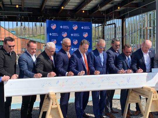 """Event attendees, including FC Cincinnati ownership, gather to sign the final steel beam to be installed in the soccer club's Milford, Ohio training facility. The """"topping off"""" ceremony was held on Tuesday, April 16."""