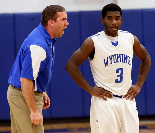 Wyoming Hoops 0122 Sports Tuesday January 21, 2014: Wyoming coach Matt Rooks talks with Ahmad Frost (3) against Madeira in the second period. Madeira High School battles Wyoming High School in a basketball game at Wyoming High School Tuesday January 21, 2014 in Wyoming. The Enquirer/ Joseph Fuqua II