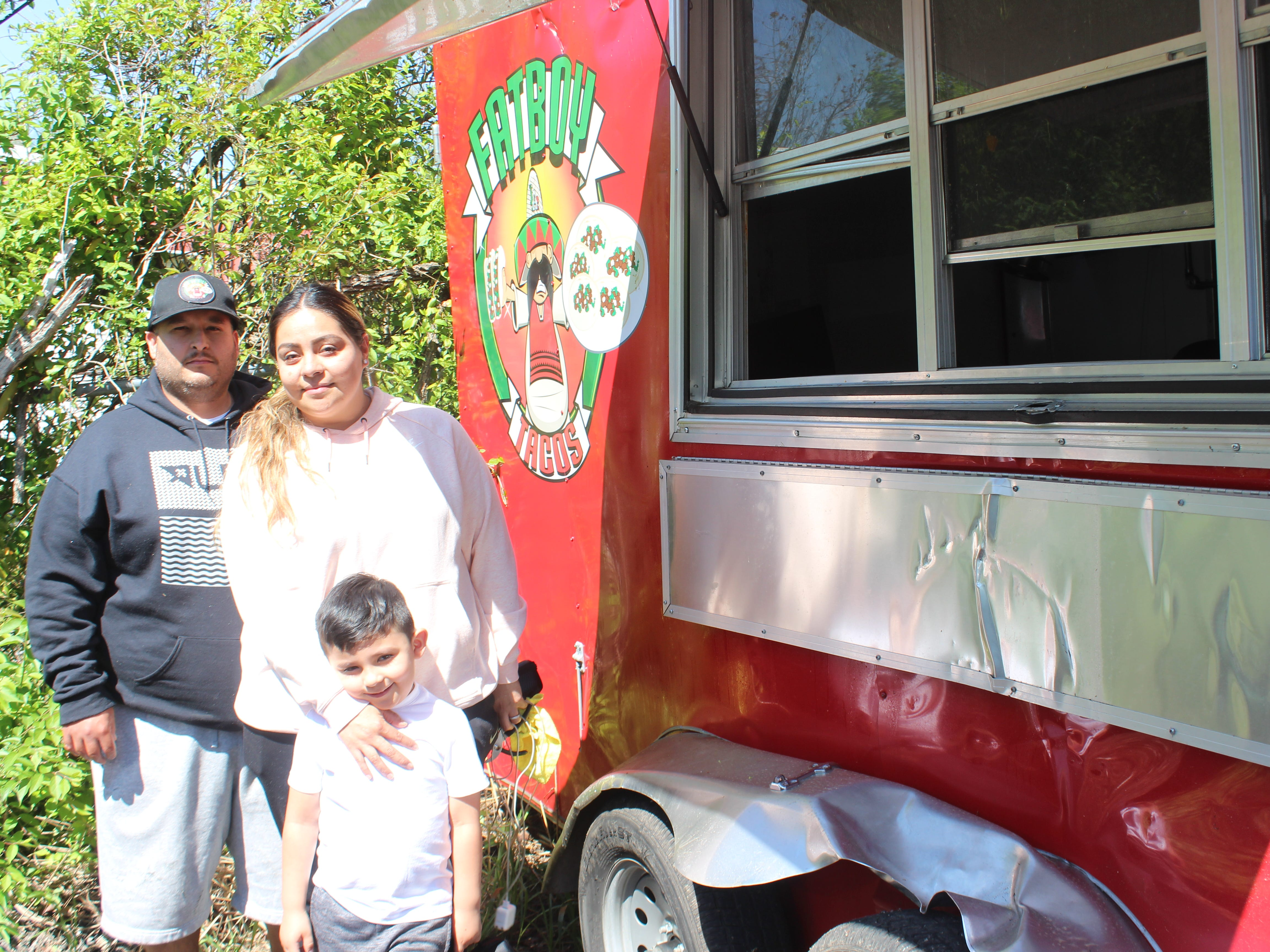 Adrian and Diana Gonzalez and their son Adrian Jr. stand outside the wrecked remains of their Fatboy Taco trailer, the family business that was destroyed in an accident in Clarksville on Saturday, April 13, 2019.