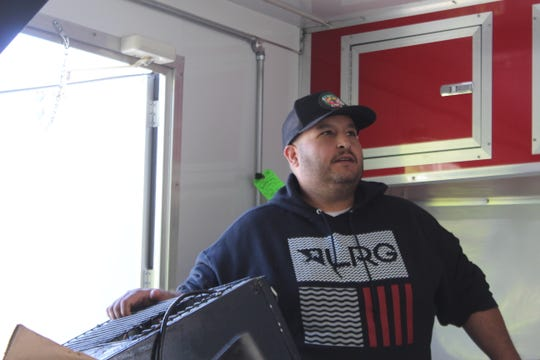 Adrian Gonzalez of Clarksville inspects the damage to his Fatboy Tacos trailer after it was totaled in a wreck.