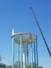 The old water storage tank on Alfred Thun Road is dismantled on Monday, April 15, 2019. Work is expected to wrap up Thursday.