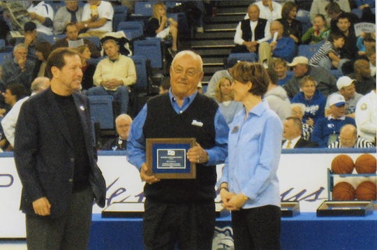 Bill Coldiron, center, accepts Drake University's Double D Award from David Maxwell and Sandy Hatfield Clubb during the halftime of a Drake basketball game in 2008. Coldiron graduated from Drake in 1955 and earned a master's degree from the school in 1968.