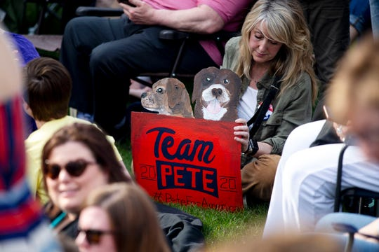 A woman holds a homemade sign for Pete Buttigieg, the mayor of South Bend, Ind., with his dogs, Truman and Buddy, on Tuesday, April 16, 2019, before the start of a rally at Franklin Junior High School in Des Moines. This is Buttigieg's first event in Des Moines since announcing his campaign for president.