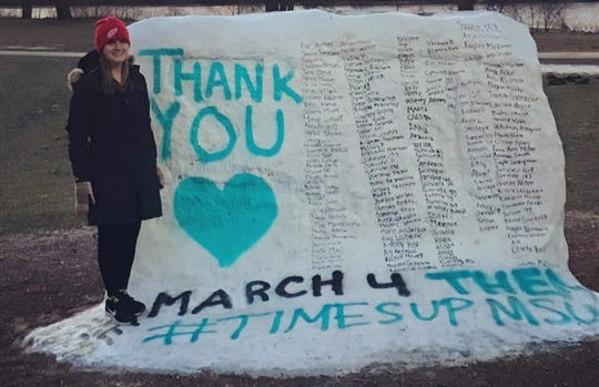 Kate Mahon poses for a photo beside a rock on the Michigan State University campus that includes the names of all the women and girls who were assaulted by sports medicine doctor Larry Nassar. She's found strength in speaking out and becoming an advocate.