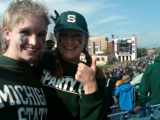 Sisters Kate and Tara Mahon cheer for the Spartans together at a Michigan State University football game.