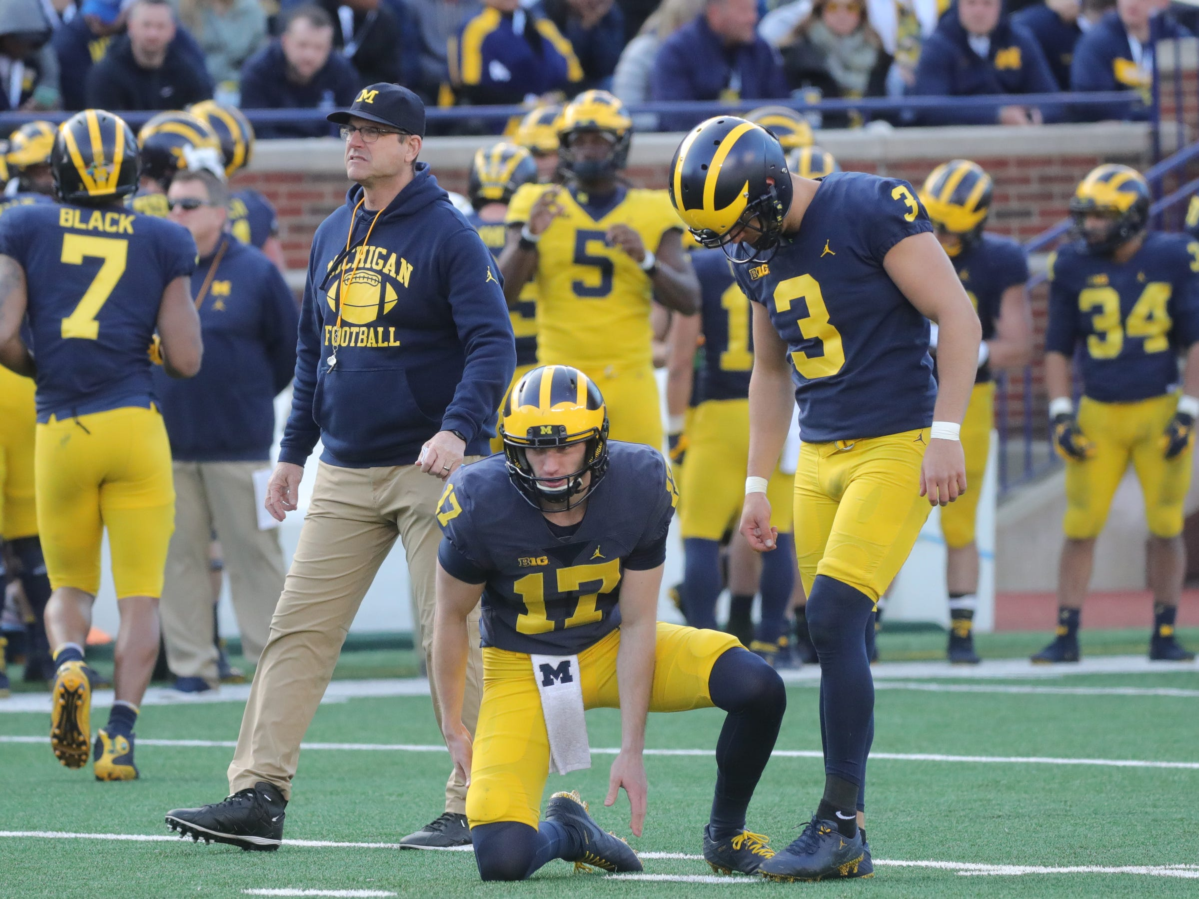 Jim Harbaugh walks by as Michigan holder Will Hart and kicker Quinn Nordin line up a field goal during the spring game Saturday, April 13, 2019 at Michigan Stadium in Ann Arbor.