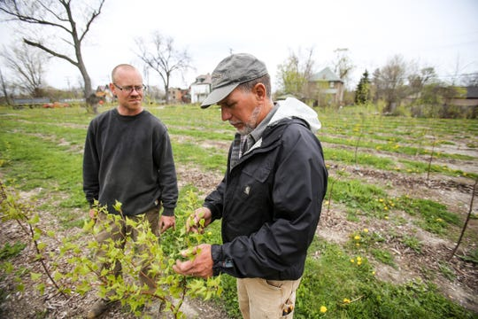 Mike Score, president of Hantz Farms, and Andy Williams, manager of Hantz Farms, walk through the east village neighborhood where Hantz Woodlands are located in east Detroit on Wednesday, May 4, 2016. Hantz Farms is trying to purchase the remaining city-owned parcels in the area.