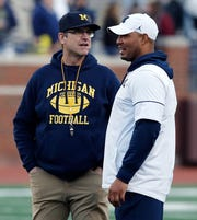 Jim Harbaugh, left, and Josh Gattis talk during the spring game in April.