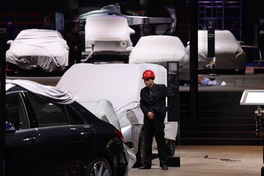 A worker stands near covered vehicles in a hall of the Auto Shanghai 2019 show in Shanghai. Automakers are showcasing electric SUVs and sedans with more driving range and luxury features at the Shanghai auto show, trying to appeal to Chinese buyers in their biggest market as Beijing slashes subsidies that have propelled demand.(AP Photo/Ng Han Guan, File)