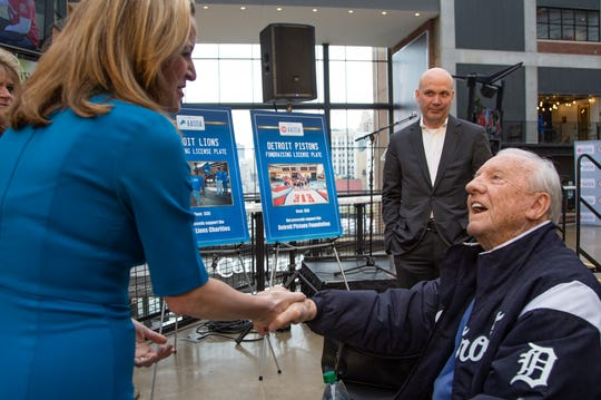 The Secretary of State Jocelyn Benson shakes hands with Tiger great Al Kaline before she announces new Detroit sports license plates as an option for purchase Monday, April 16, 2019 during a press conference at Little Caesars Arena in Detroit.