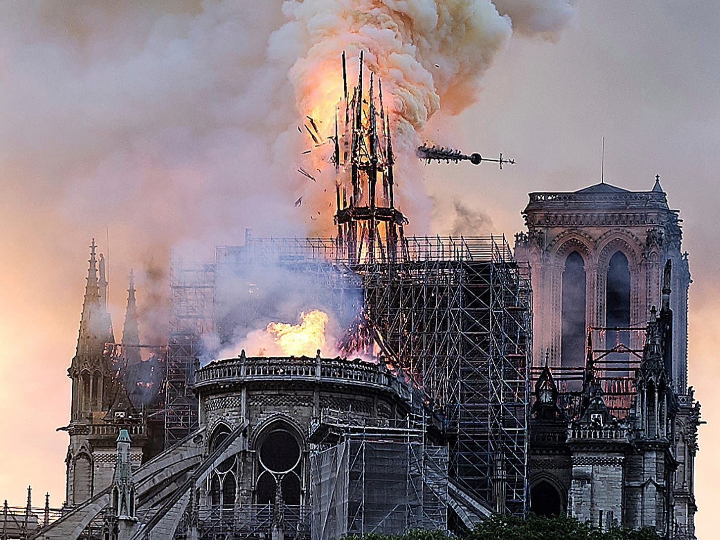 Flames and smoke rise as the spire on Notre Dame cathedral collapses in Paris, Monday, April 15, 2019. Massive plumes of yellow brown smoke is filling the air above Notre Dame Cathedral and ash is falling on tourists and others around the island that marks the center of Paris.
