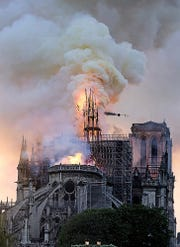 Flames and smoke rise as the spire on Notre Dame cathedral collapses in Paris, Monday, April 15, 2019.