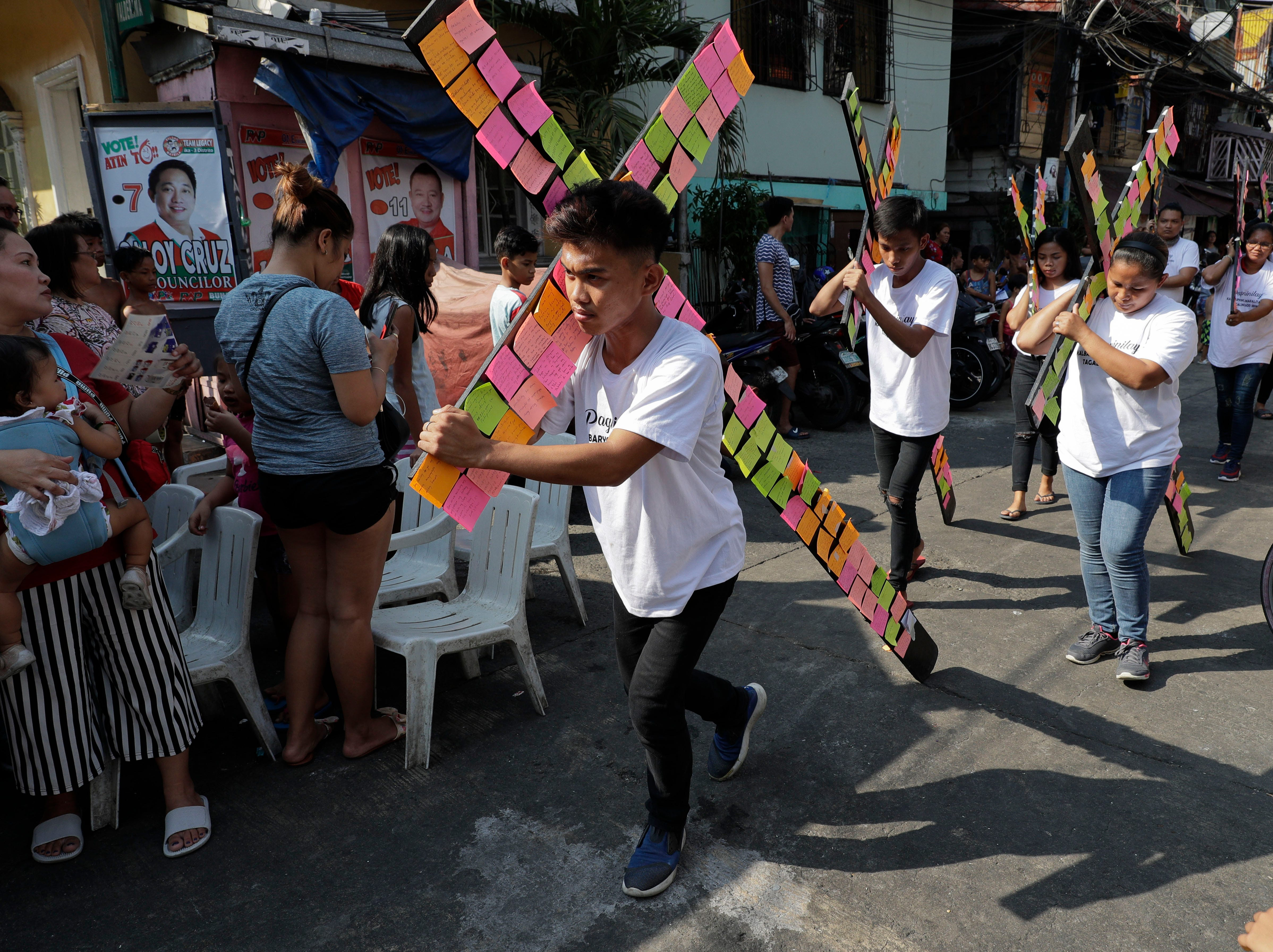 Protesters carry a wooden cross with paper notes of the wishes, concerns and problems of the urban poor during a rally on Holy Tuesday, April 16, 2019. The group said the event is held in a slum area to dramatize the plight of the urban poor under the government of Philippine President Rodrigo Duterte.