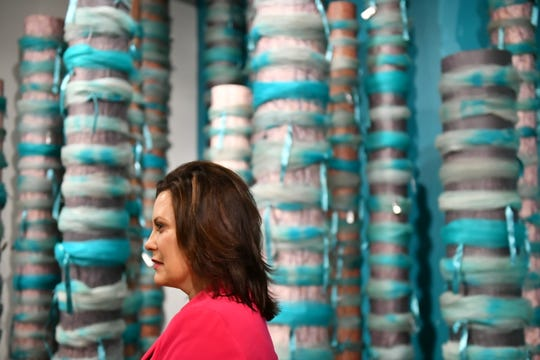 """Michigan Governor Gretchen Whitmer walks past an installation of re-created trees adorned with teal ribbons taken from campus trees during a tour of """"Finding Our Voice: Sister Survivors Speak"""" at the Michigan State University Museum, April 16, 2019."""