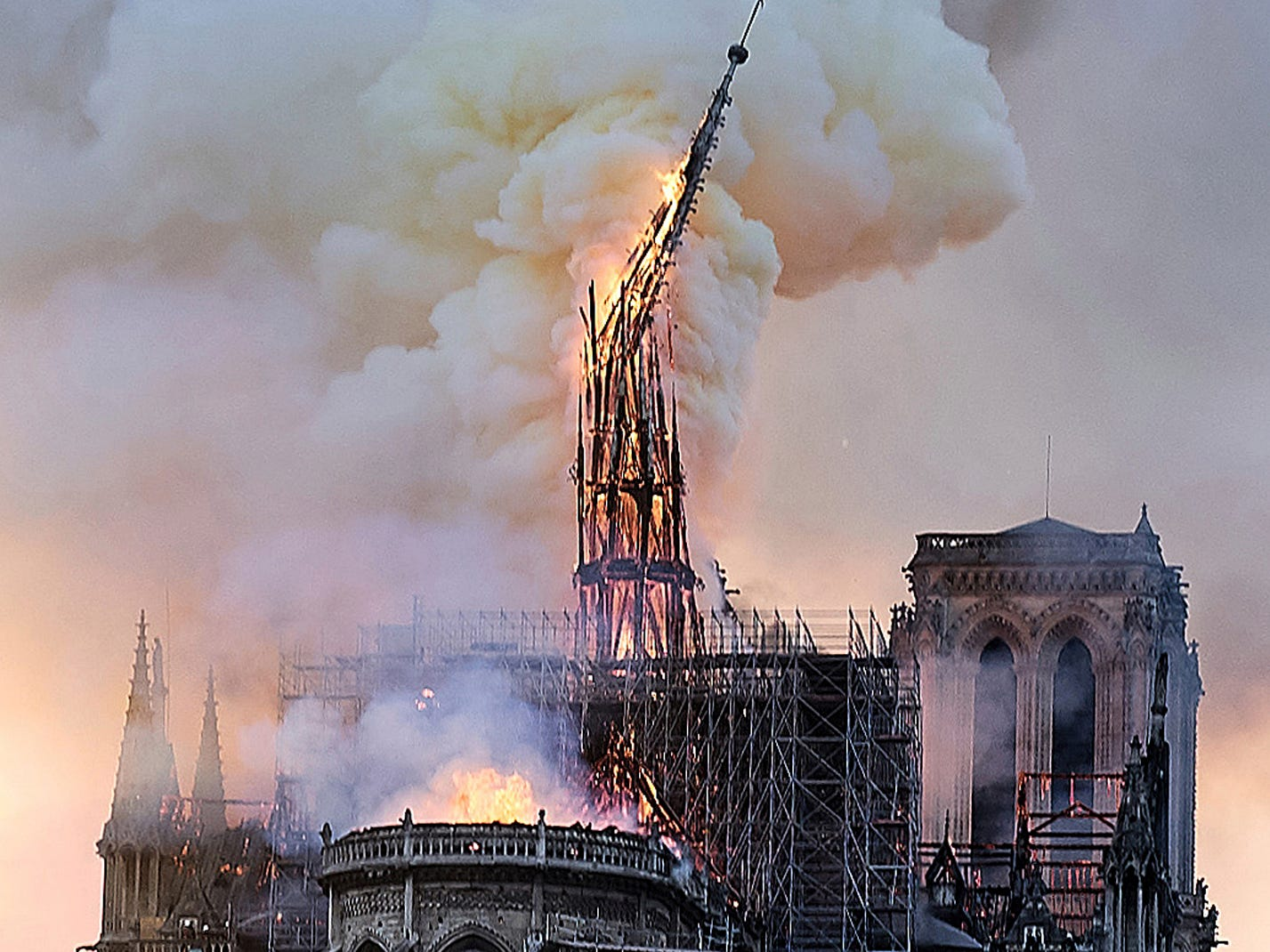 Flames and smoke rise as the spire on Notre Dame cathedral collapses in Paris, Monday, April 15, 2019. Massive plumes of yellow brown smoke is filling the air above Notre Dame Cathedral and ash is falling on tourists and others around the island that marks the center of Paris