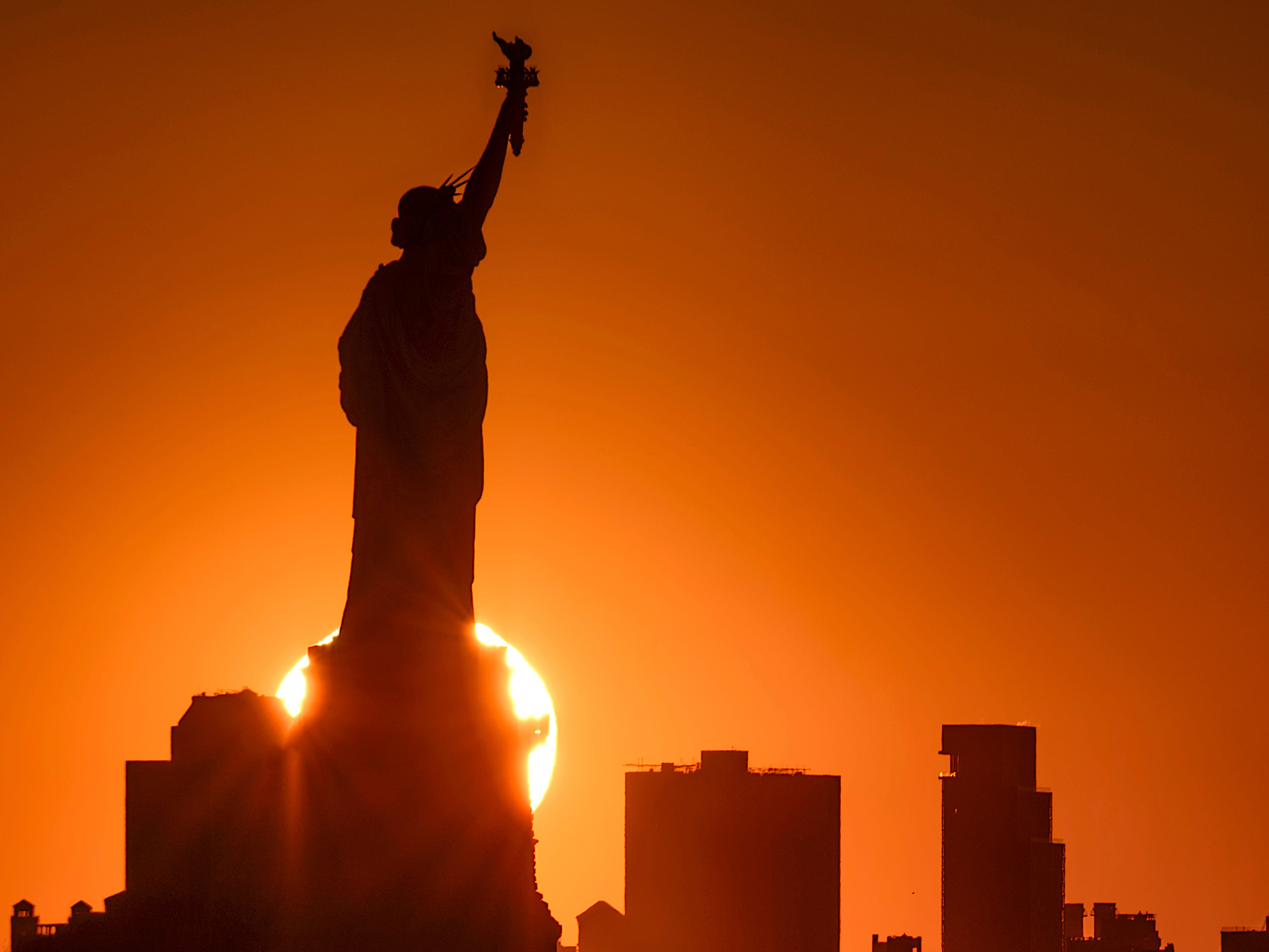 Sunrise behind the Brooklyn borough of New York City silhouettes the Statue of Liberty as captured from Jersey City, N.J., Tuesday, April 16, 2019.