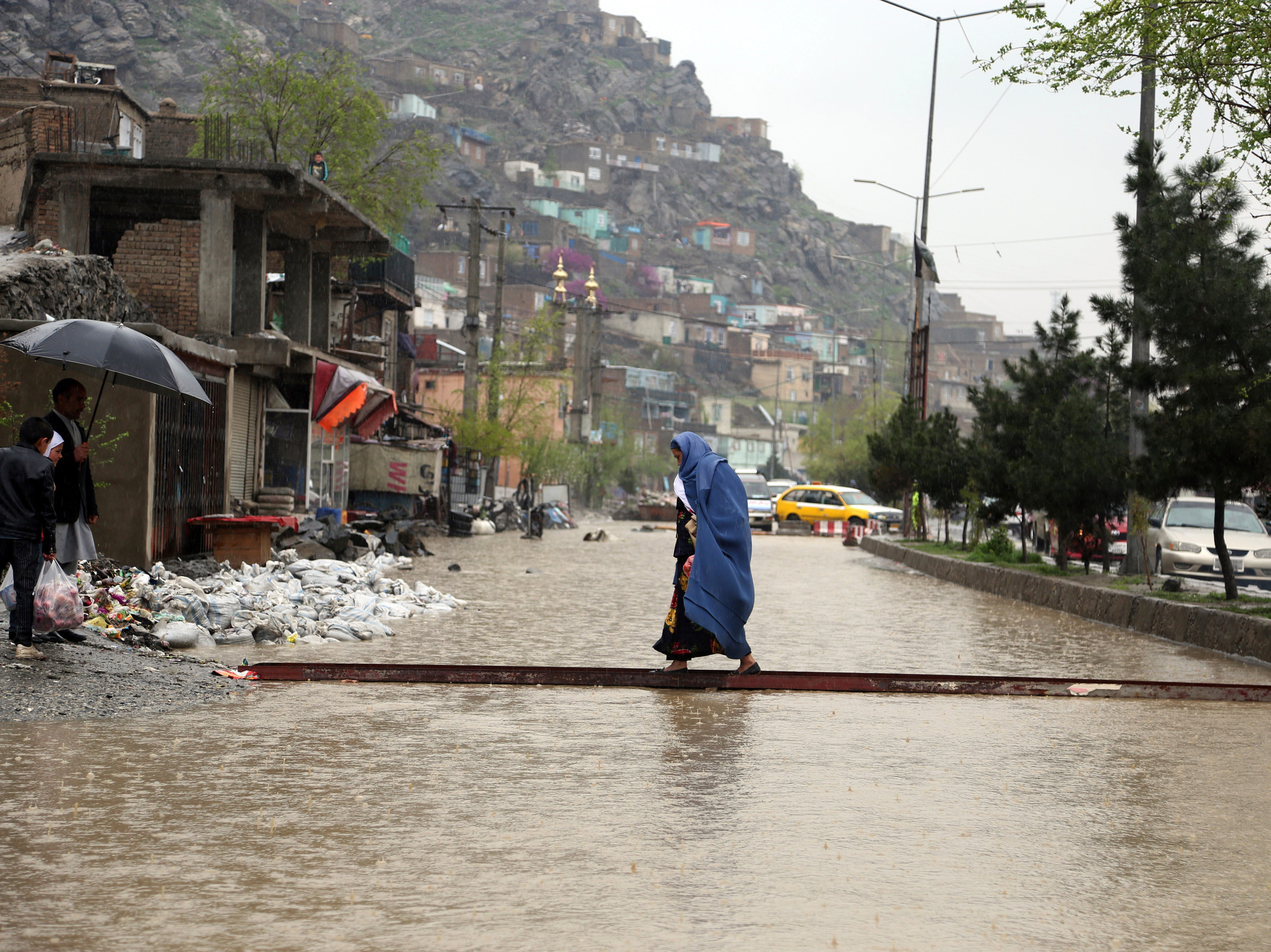 An Afghan woman walks through flood water as heavy rain falls in Kabul, Afghanistan, Tuesday, April 16, 2019. Afghan officials say at least five more people have been killed and 17 are missing as a new wave of heavy rains and flooding swept across the country's western Herat province.