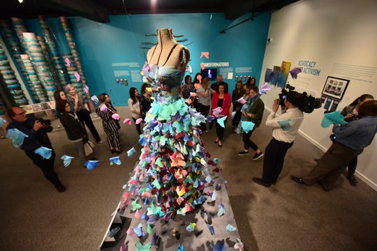 "Visitors walk past a sculpture called ""Ten Feet Tall"" created by sister survivor Alexandra Bourque during a tour of ""Finding Our Voice: Sister Survivors Speak"" at the Michigan State University Museum, April 16, 2019. The sculpture was made of 300 tie-dyed silk butterflies."