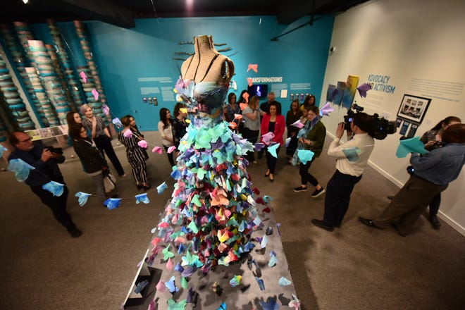 """Visitors walk past a sculpture called """"Ten Feet Tall"""" created by sister survivor Alexandra Bourque during a tour of """"Finding Our Voice: Sister Survivors Speak"""" at the Michigan State University Museum, April 16, 2019. The sculpture was made of 300 tie-dyed silk butterflies."""