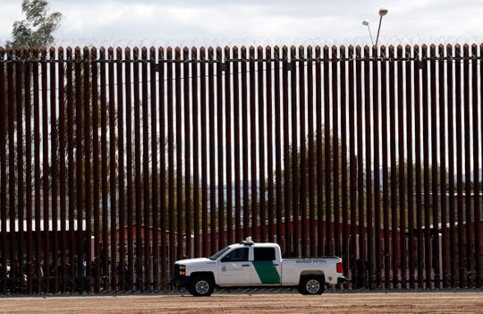 In this April 5, 2019, file photo, a U.S. Customs and Border Protection vehicle sits near the wall as President Donald Trump visits a new section of the border wall with Mexico in Calexico.