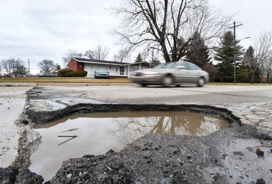 A large, deep pothole, 3 feet wide, is seen on  the westbound I-696 service drive at Belanger in Warren, Michigan on February 21, 2018.