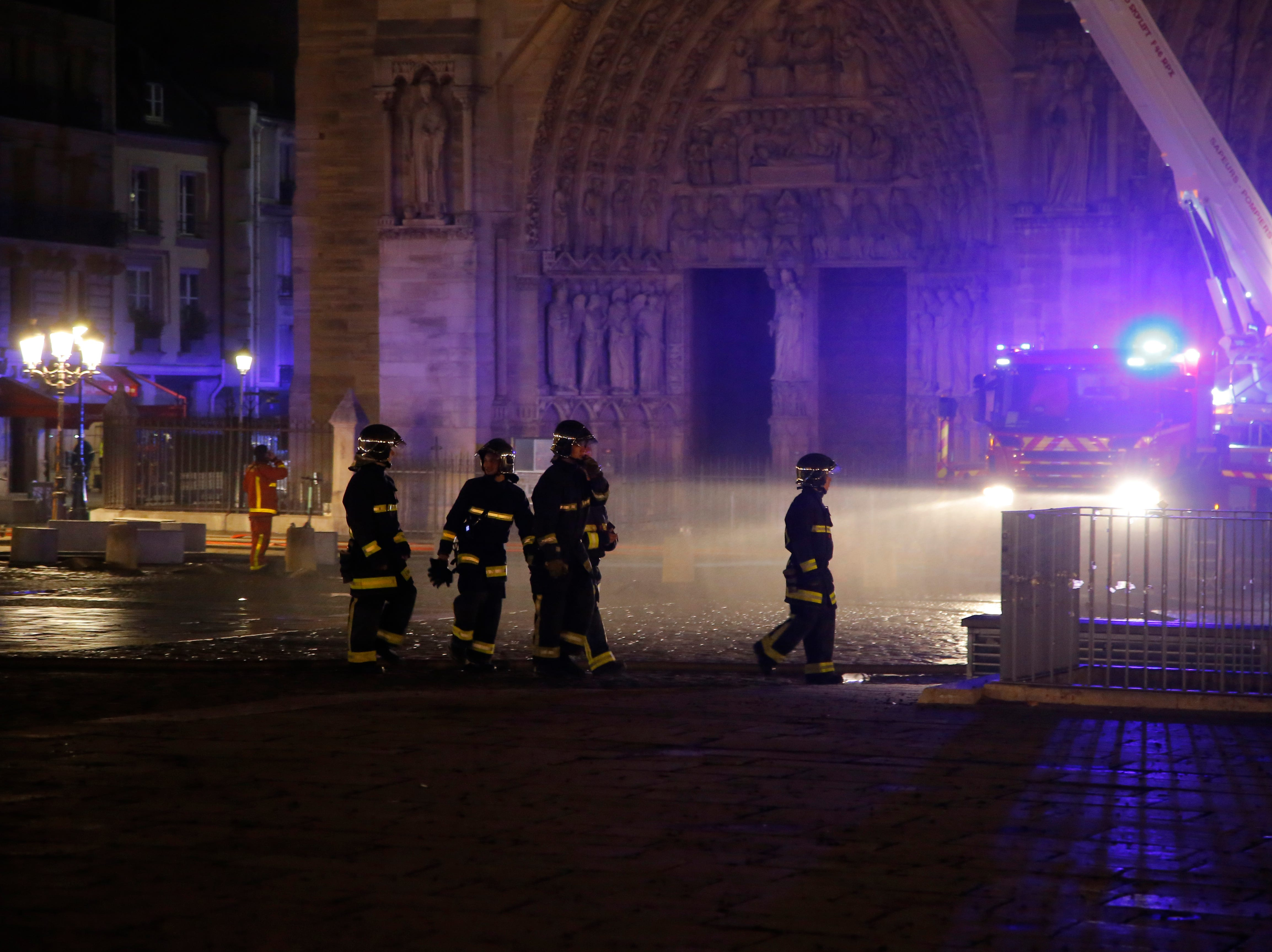 Fire fighters work outside Notre Dame cathedral burning in Paris, Monday, April 15, 2019. A catastrophic fire engulfed the upper reaches of Paris' soaring Notre Dame Cathedral as it was undergoing renovations Monday, threatening one of the greatest architectural treasures of the Western world as tourists and Parisians looked on aghast from the streets below.