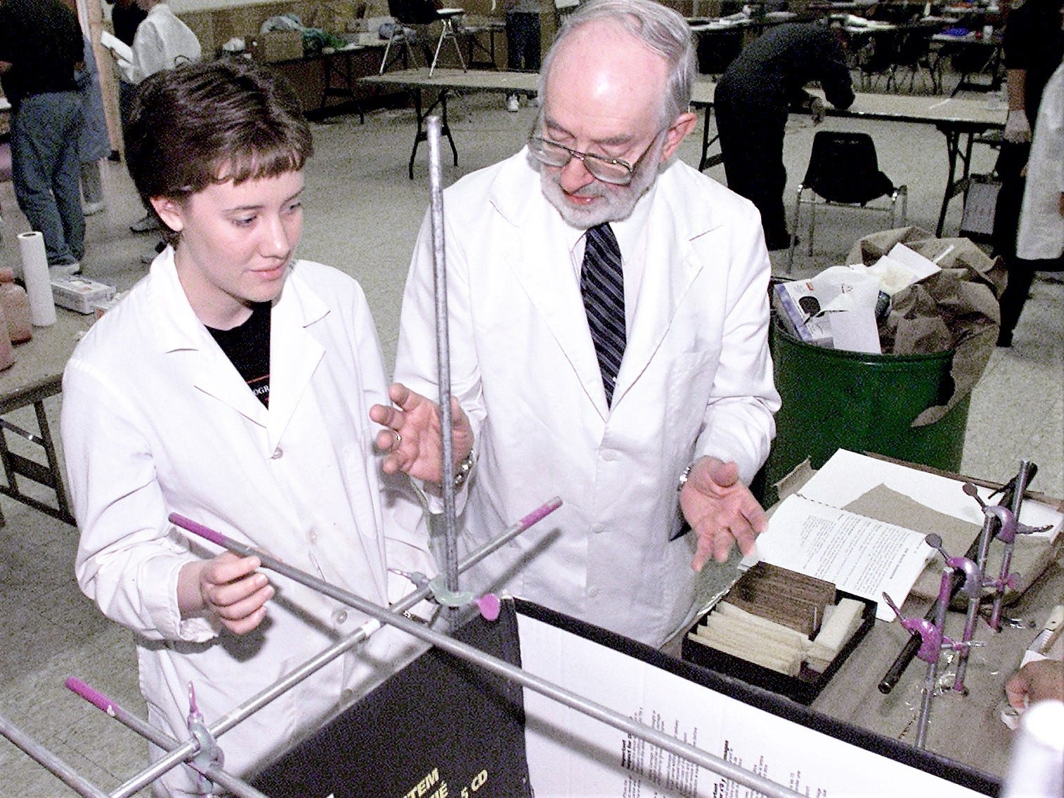 Herbert MacDonell tells Stacy Toup how an experiment will be conducted during a bloodstain seminar in Corning. In the experiment, a bullet is fired through a blood-soaked sponge so that the pattern of blood sprayed during impact can be observed on a white piece of paper.