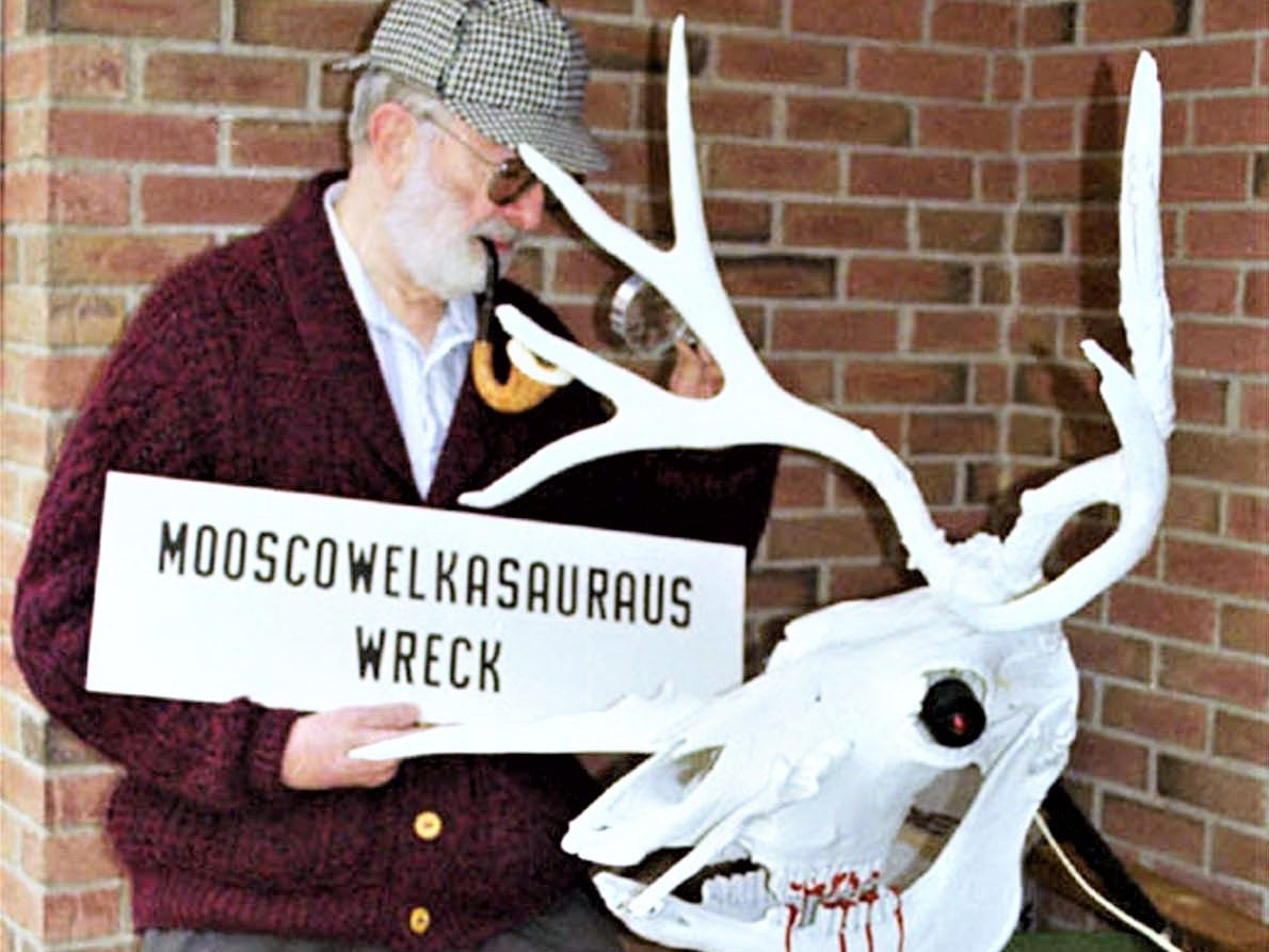 """Forensic scientist Herbert MacDonell of Corning donned his Sherlock Holmes hat and pipe to examine his creation """"Mooscowelkasauraus Wreck"""" at his home."""