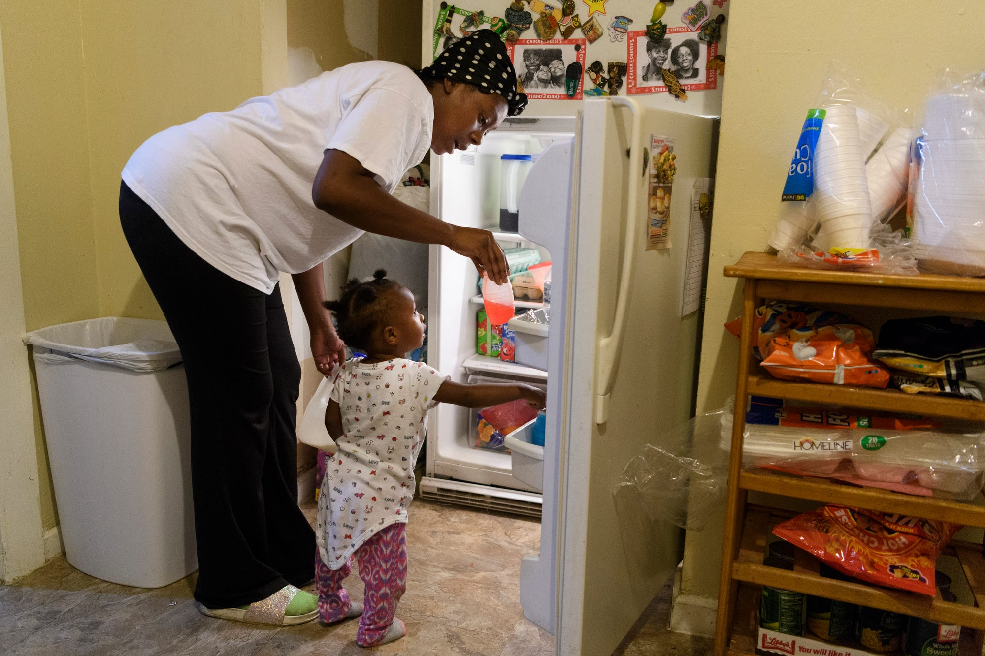 Tamisha Dilworth hands her youngest daughter Teresa, 1, a drink before serving her three children dinner at her father's house in Evansville, Ind., Monday, Sept. 24, 2018. Dilworth saved money by moving out of a three-bedroom apartment to live with her father, Robert Bradley, not pictured, for seven months while working through the nearly year-long  Habitat for Humanity program.