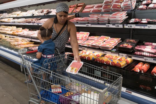 """Mari Milan selects groceries with her daughter Roze at Ruler Food Tuesday, April 16, 2019. Milan was taking advantage of the new """"Feeding the Promise Zone"""" program that uses the TED Trolley to transport individuals living in and around Garfield Commons in Jacobsville to pick up groceries once a week."""