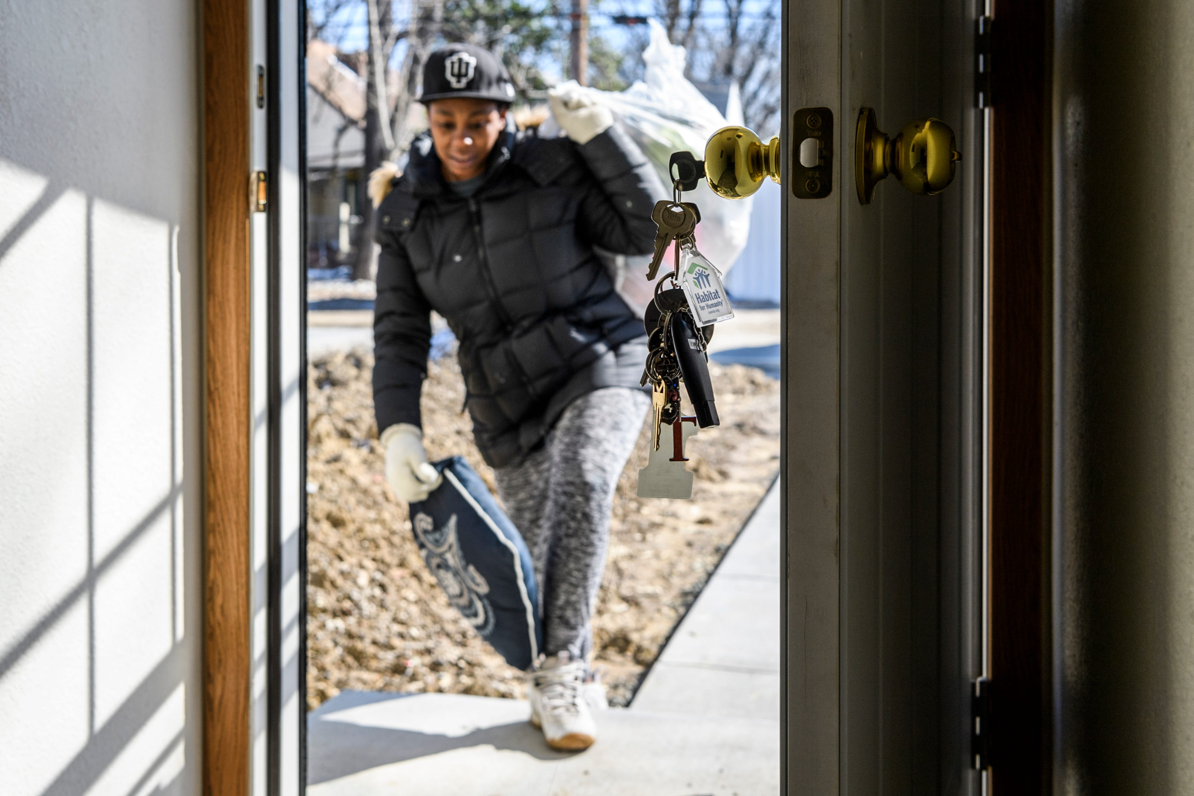 Keys featuring a house-shaped keychain with the Habitat for Humanity logo dangle from the back door as Tamisha Dilworth carries a pillow and a bag full of clothes into her new house, Monday morning, March 4, 2019. She promptly began moving her family's items into their new space after signing paperwork and receiving the keys.