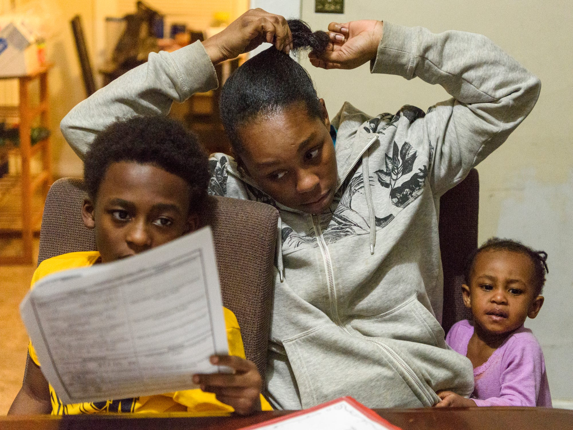 Tamisha Dilworth, center, looks over her son Travon's homework as her daughter Teresa vies for her attention, Wednesday evening, Feb. 13, 2019. Dilworth works long hours every weekend as a Certified Nursing Assistant, which allows her to help her children get to and from school, do their homework and spend time together as a family on weekdays.