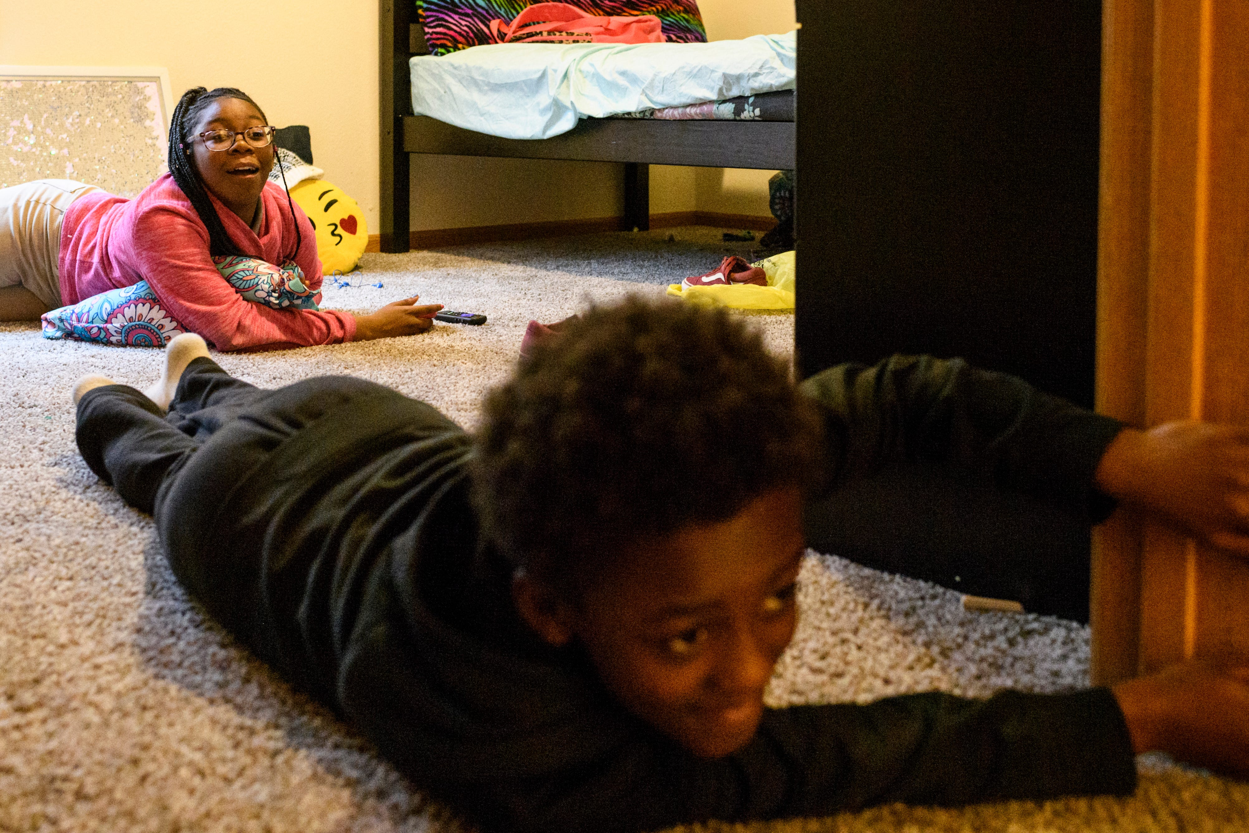 """""""Get out of my room,"""" Aliyah says as she reacts to her younger siblings Travon, front, and Teresa, not pictured, continually popping in and out of her new room while burning off their energy during playtime, Thursday evening, March 21, 2019. For the first several weeks there was an ample amount of space to run around as the family waited for the delivery of big furniture items, such as a couch and a dining room table."""