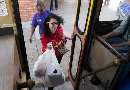 """Kaylee Ricketts boards the TED Trolley after shopping for groceries at Ruler Foods Tuesday, April 16, 2019. Ricketts was taking advantage of the new """"Feeding the Promise Zone"""" program that transports individuals living in and around Garfield Commons in Jacobsville to pick up groceries once a week."""