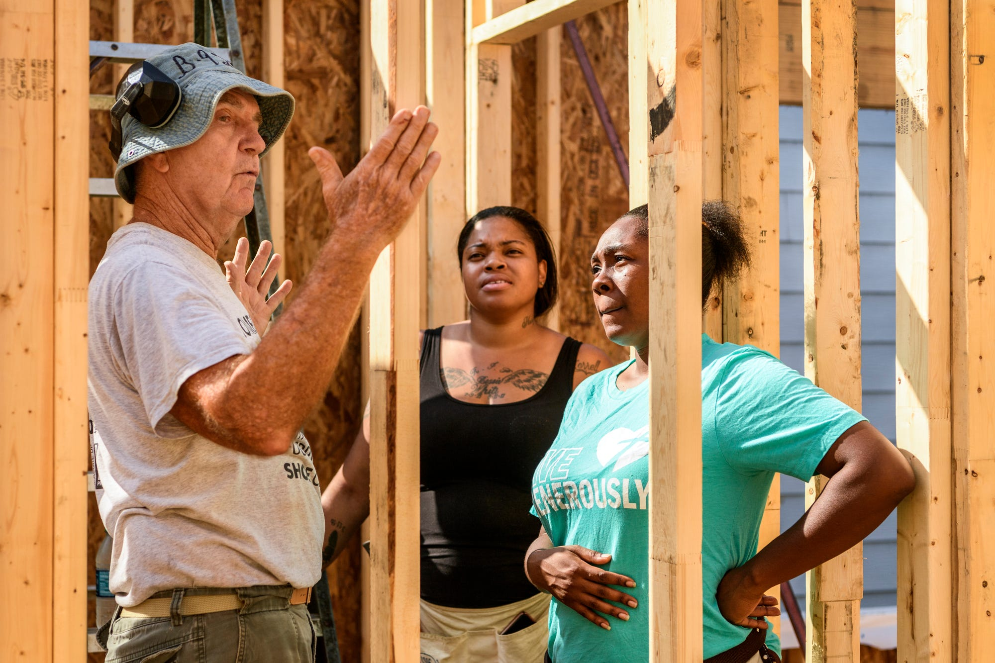 Chris Huus, a member of the Habitat Core Crew, instructs Tiffany Wilson, center, and Tamisha Dilworth, right, as they continue building the walls of Dilworth's house in Evansville's Ballard Neighborhood, Tuesday morning, Oct. 2, 2018. Wilson, who was named the 497th Habitat homeowner, and her family live down the street from Dilworth on Bedford Avenue.