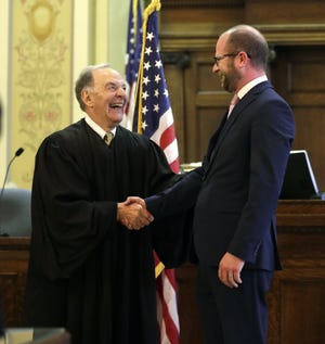 Brown County Circuit Court Judge Donald R. Zuidmulder shakes the hand of newly sworn-in Green Bay Mayor Eric Genrich following a ceremony Tuesday at the Brown County Courthouse in Green Bay.