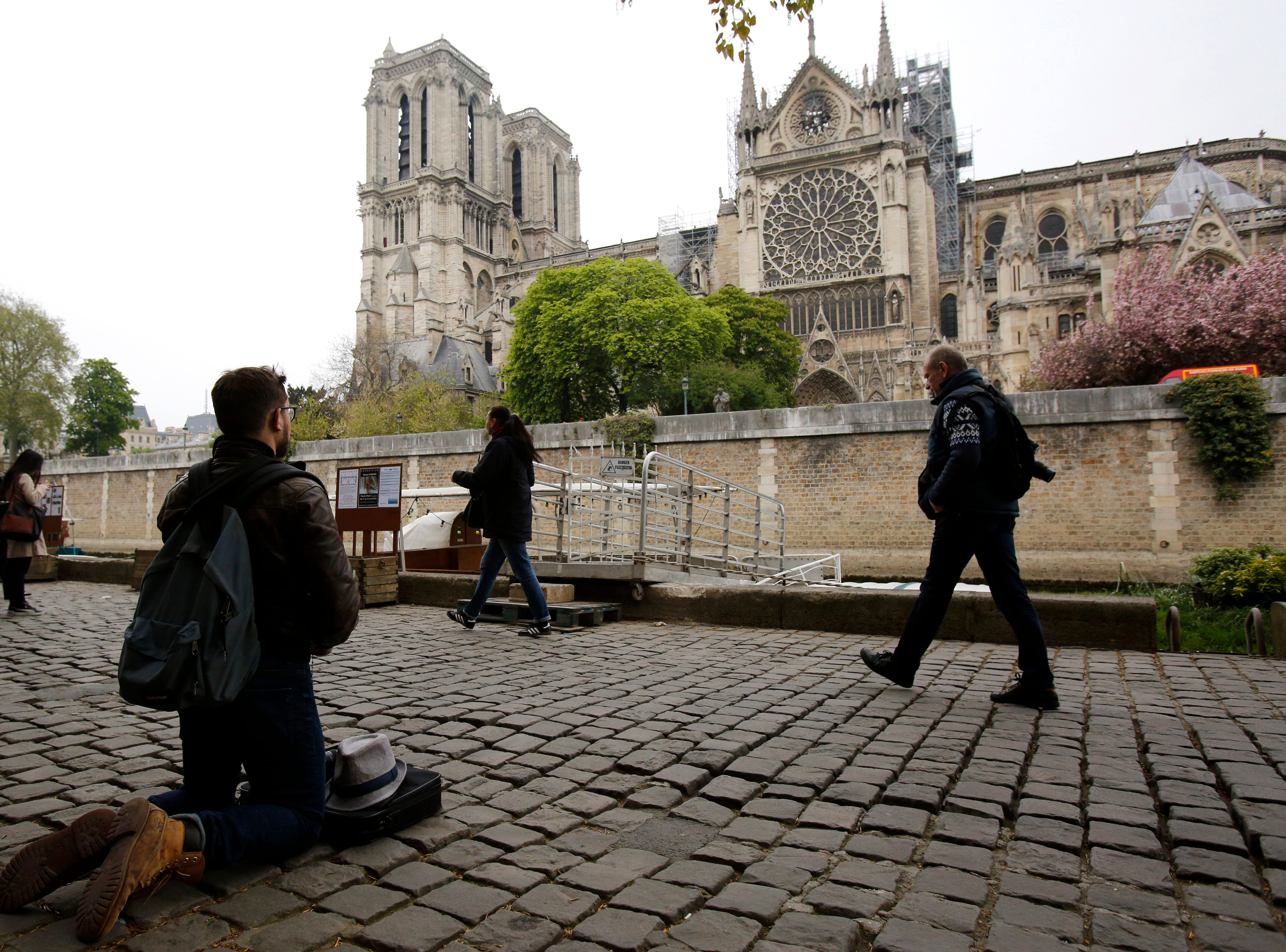 Man kneels as people came to watch and photograph the Notre Dame cathedral after the fire in Paris, Tuesday, April 16, 2019. Experts are assessing the blackened shell of Paris' iconic Notre Dame cathedral to establish next steps to save what remains after a devastating fire destroyed much of the almost 900-year-old building. With the fire that broke out Monday evening and quickly consumed the cathedral now under control, attention is turning to ensuring the structural integrity of the remaining building. (AP Photo/Christophe Ena)