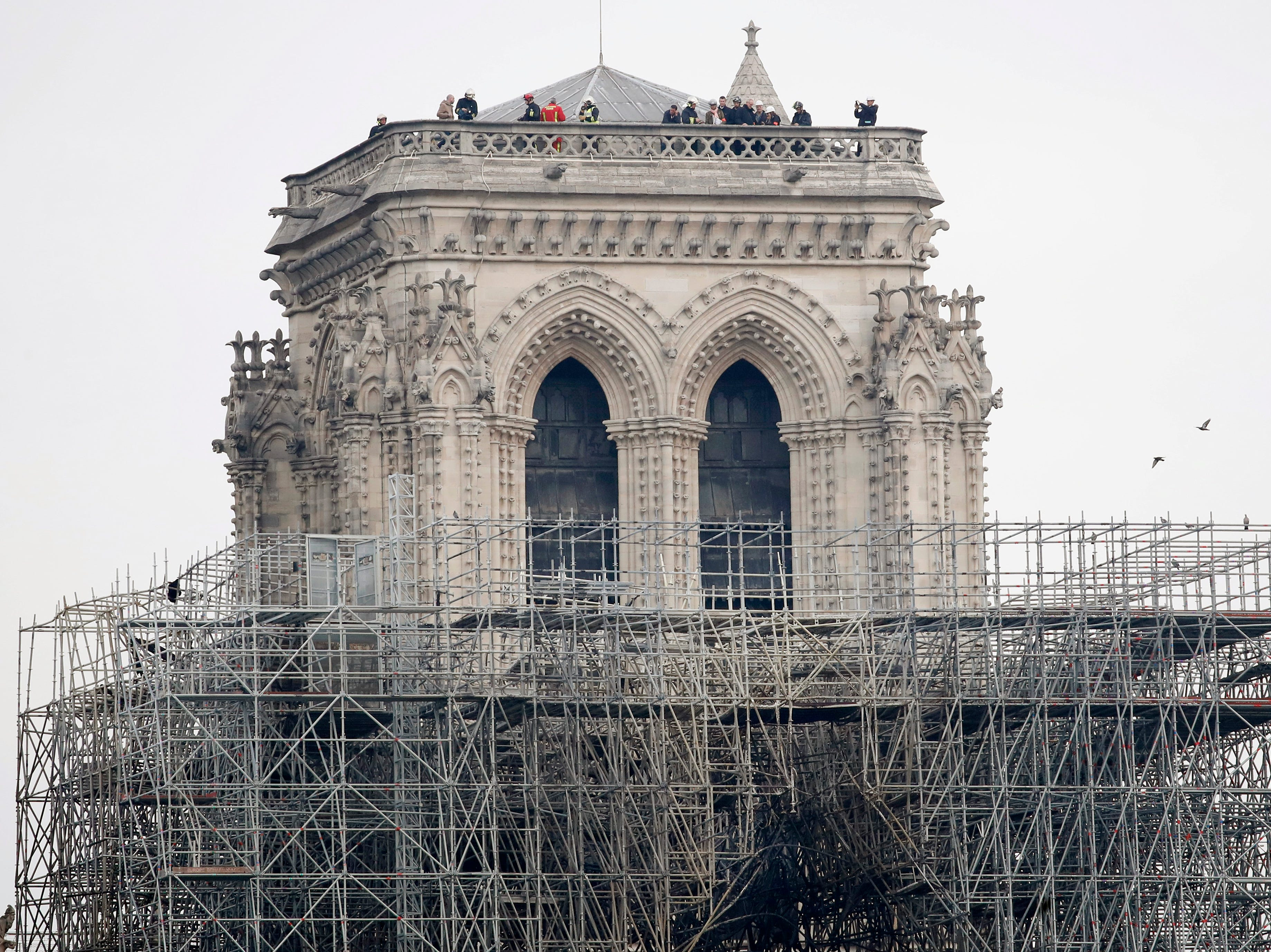 Firemen inspect the Notre Dame cathedral after the fire in Paris, Tuesday, April 16, 2019. Experts are assessing the blackened shell of Paris' iconic Notre Dame cathedral to establish next steps to save what remains after a devastating fire destroyed much of the almost 900-year-old building. With the fire that broke out Monday evening and quickly consumed the cathedral now under control, attention is turning to ensuring the structural integrity of the remaining building. (AP Photo/Christophe Enaa)