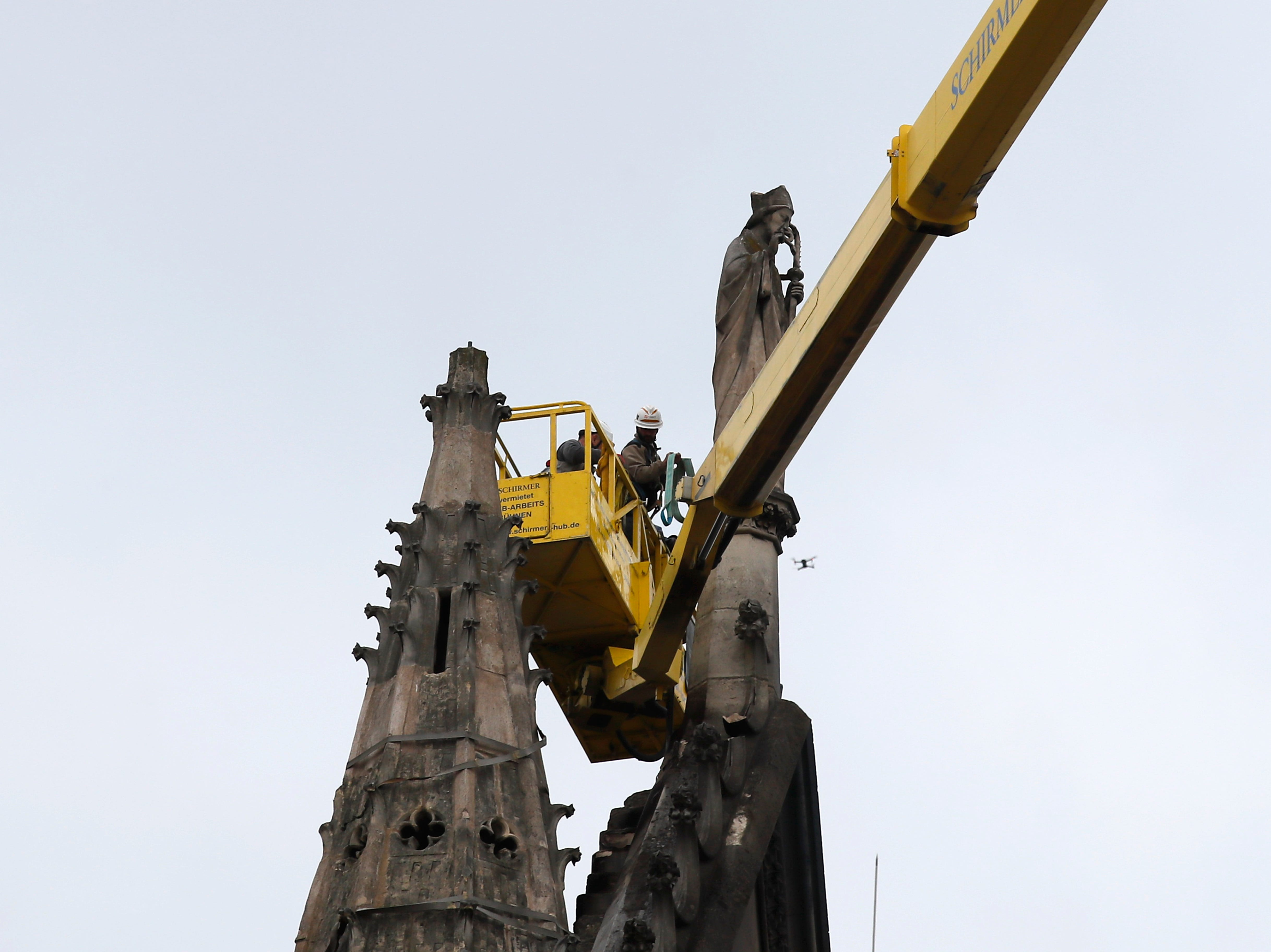 Workers stand atop a crane at Notre Dame cathedral Tuesday April 16, 2019 in Paris. Firefighters declared success Tuesday in a more than 12-hour battle to extinguish an inferno engulfing Paris' iconic Notre Dame cathedral that claimed its spire and roof, but spared its bell towers. (AP Photo/Francois Mori)