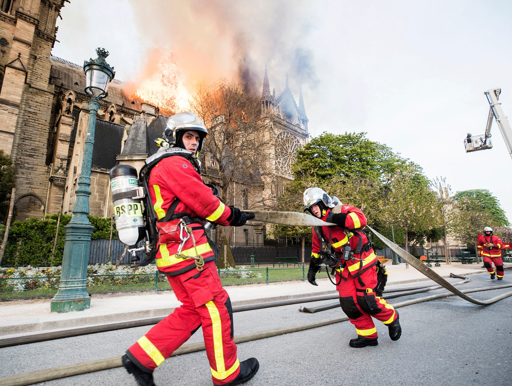 This photo provided Tuesday April 16, 2019 by the Paris Fire Brigade shows fire fighters pulling a hose by the burning Notre Dame cathedral, Monday April 15, 2019. Experts assessed the blackened shell of Paris' iconic Notre Dame Tuesday morning to establish next steps to save what remains after a devastating fire destroyed much of the cathedral that had survived almost 900 years of history. (Benoit Moser, BSPP via AP)